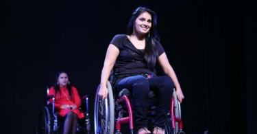 A photos of Virali Modi in a wheelchair on stage, sitting on a wheelchair and smiling. Behind her, another woman is sitting on a wheelchair. The second woman is blurry and seems to be waiting.