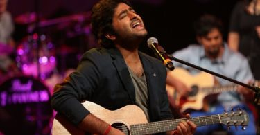 This is a photo of singer Arijit Singh sitting in front of a microphone and singing. He is holding a guitar in his hands.