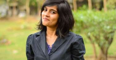 A photo of Kalyani Khona standing and smiling knowingly at the camera.