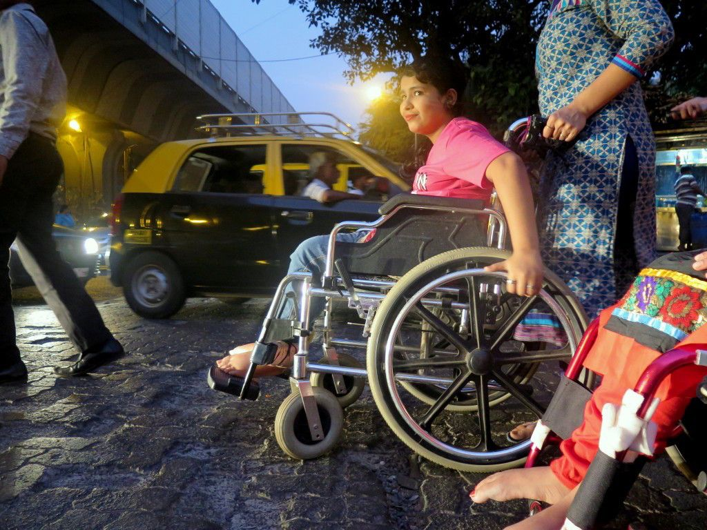 A photo of a girl on a wheelchair crossing a busy road.