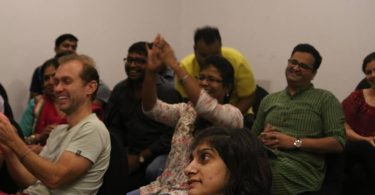 A group of people are seated as part of the audience at one of Inclov's Social Spaces events. Some of them are smiling, while others are laughing and clapping their hands.
