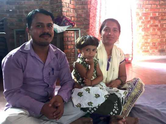 A photograph of Sharif and Nilofer, sitting crosslegged on the floor of their home, looking directly at the camera with smiles on their faces. Their daughter, a young child, sits between them.