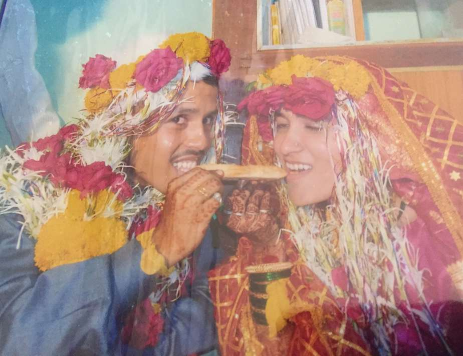 Sharif and Nilofer on their wedding day. They are both decorated with flowers and are sharing a sweet.