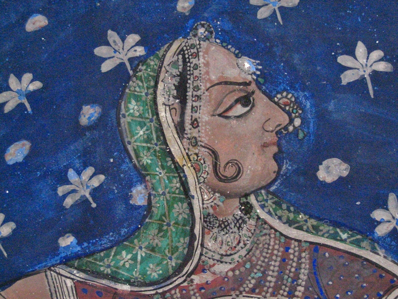 The photo is a close up of a wall painting in Juna Mahal, Rajasthan, and shows a woman's face and shoulders against a blue background. She is wearing a green veil and has many ornaments on around her neck and head.