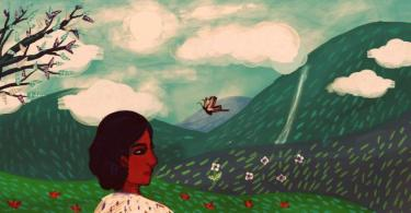 A young woman looks at mountain vistas – there are many clouds in the sky and a tree stands some distance away from her.