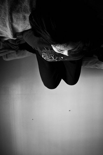 Description: This is a black and white photograph of a person lying upside down in a bed, looking at a blank wall. Credit: Sodanie Chea via Flickr, CC BY 2.0.