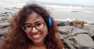 In this picture of Durga, she is smiling, and wearing a pink top and blue headphones. In the background, there is the sea, and to her right, a small brown dog sniffs around the rocks.