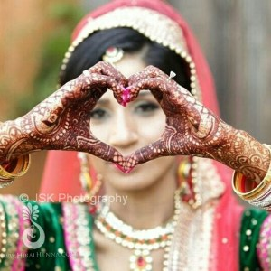 An Indian bride with her hands in a heart shape, showing her mehndi