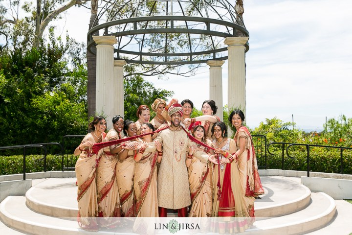 Bridesmaids at an Indian wedding iving the groom a hard time - pulling on his dupatta.