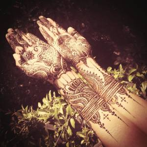 An Indian bride posing her arms and hands to show off her beautiful mehndi design