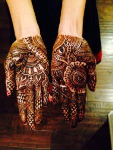 Intricate and heavy coverage mehndi design on an Indian bride's two hands only, not on the arms