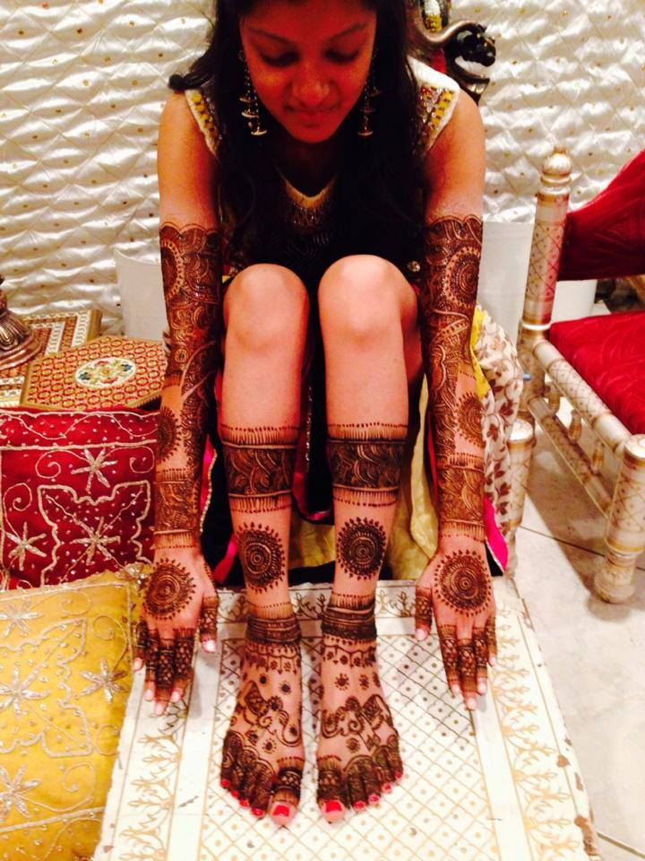 An Indian bride's photo of her hands, arms, feet, and legs, showing her beautiful mehndi design by Neha Assar.