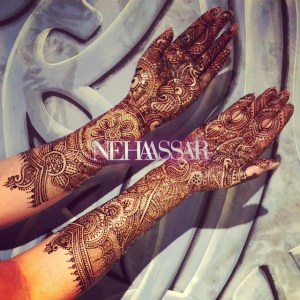 Mehndi by Neha Assar on a bride's hands up to her forearm