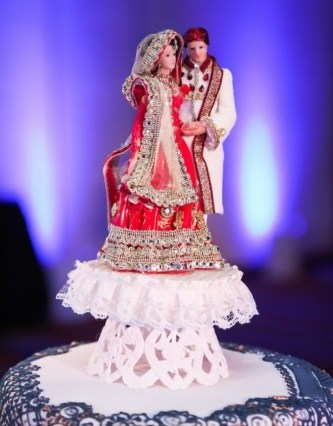 Indian bride and groom cake topper with the clothing designed like the bride and groom's actual lehenga and sherwani