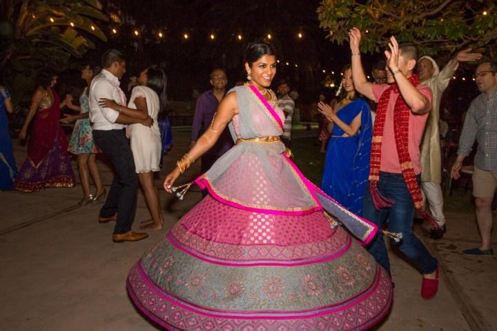Indian bride dancing in her pink lehenga at her wedding reception
