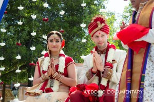 Indian bride and groom praying during their Hindu wedding ceremony.