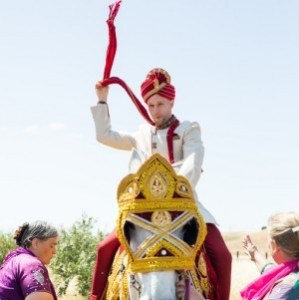 Groom waving his dupatta like a lasso while on a horse for his Indian wedding baraat