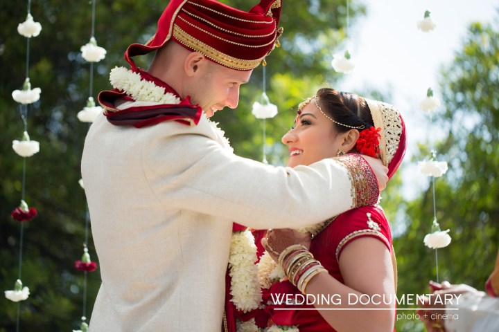 Groom putting the mangal sutra on his Indian bride during their Hindu wedding ceremony.