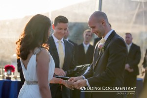 Groom putting ring on his wife's finger during the wedding ceremony.