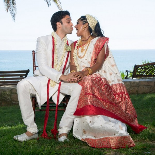Bride and groom sitting on a bench kissing