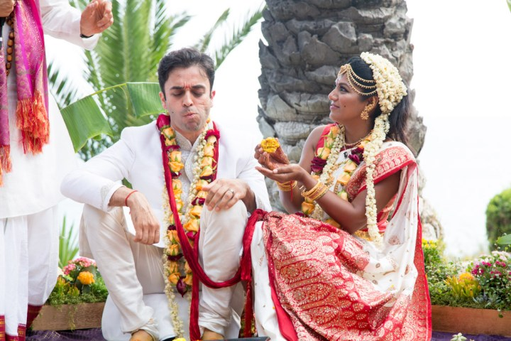 The bride and groom feeding each other sweets afer their Hindu wedding ceremony