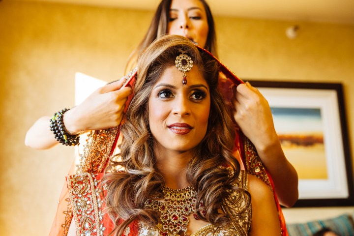 An Indian bride draping her dupatta on her head for her Hindu wedding ceremony.