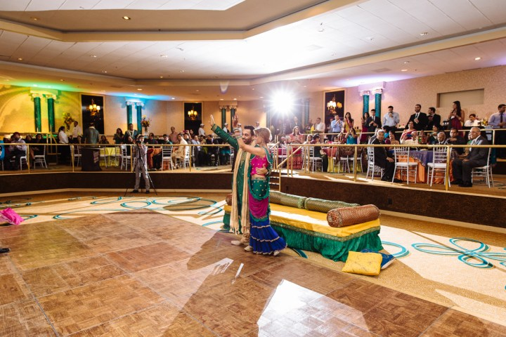 An Indian bride looking around the ballroom at her guests at her Indian wedding sangeet-garba.