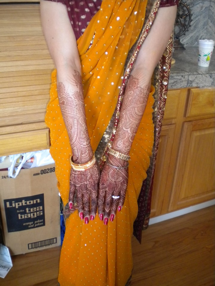 Indian bride's hands with mehndi all the way to her elbows