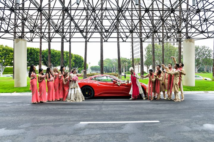 Indian wedding bridesmaids and groomsmen funny photo in front of fancy car for Indian wedding baraat