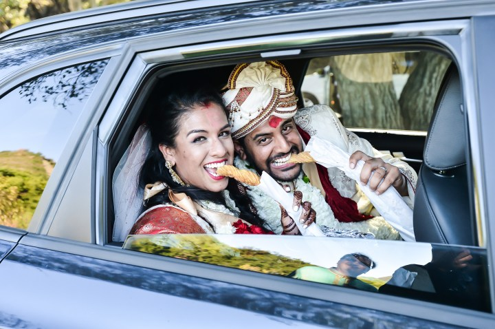 Indian bride and groom eating churros on their way out after the vidai