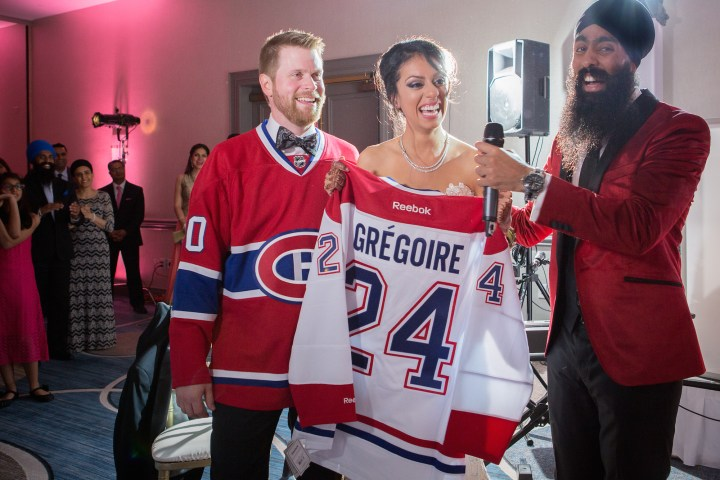An Indian-Canadian, Sikh bride smiling, wearing a white wedding gown, holding up a hockey jersey, with her groom standing next to her.