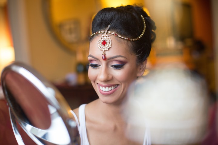 Indian bride smiling, wearing her tikka