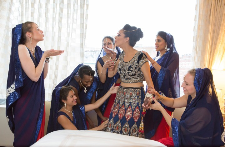 Indian bride having a playful moment with her bridesmaids