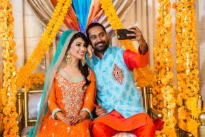 Indian bride and groom wearing bright colors, taking a selfie at their mehndi function