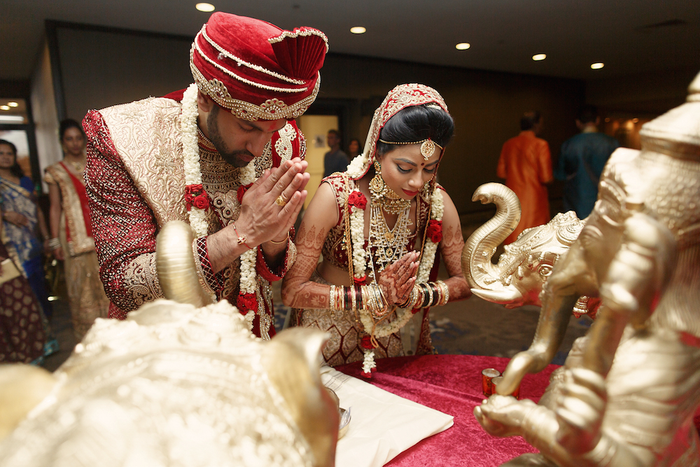 Indian couple praying at their wedding