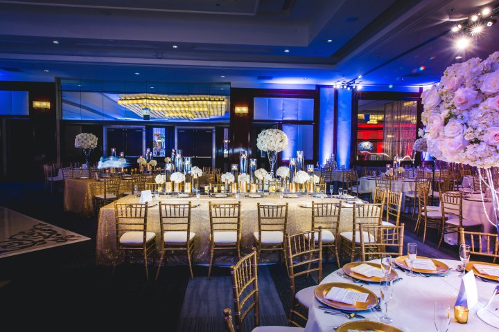 a Ballroom at the Westin Long Beach decorated for a Indian wedding reception with gold chiavari chairs and kings tables with tall floral centerpieces.