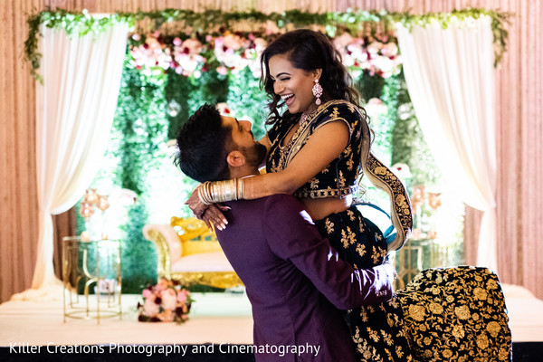 Indian groom wearing a tuxedo lifting his new bride who is wearing a glittery lehenga, as they both smile.