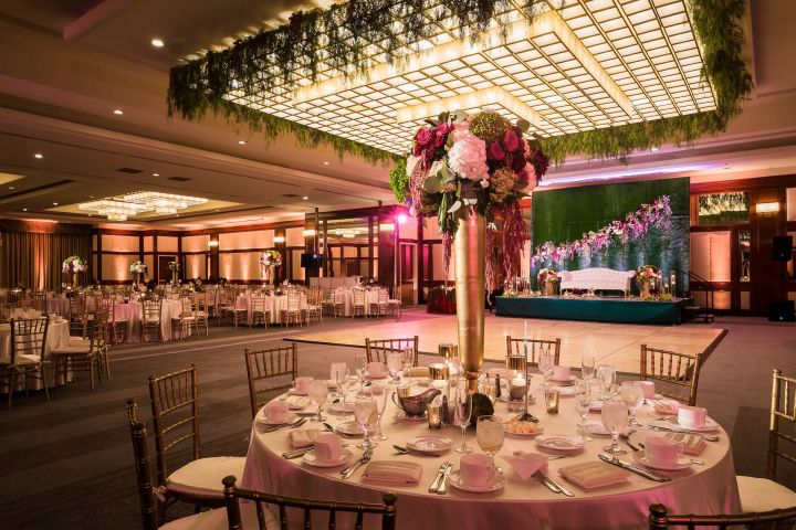 a ballroom dressed with tables, chairs, a dance floor, a stage with a couch for the newlyweds, and floral decor for a wedding reception.
