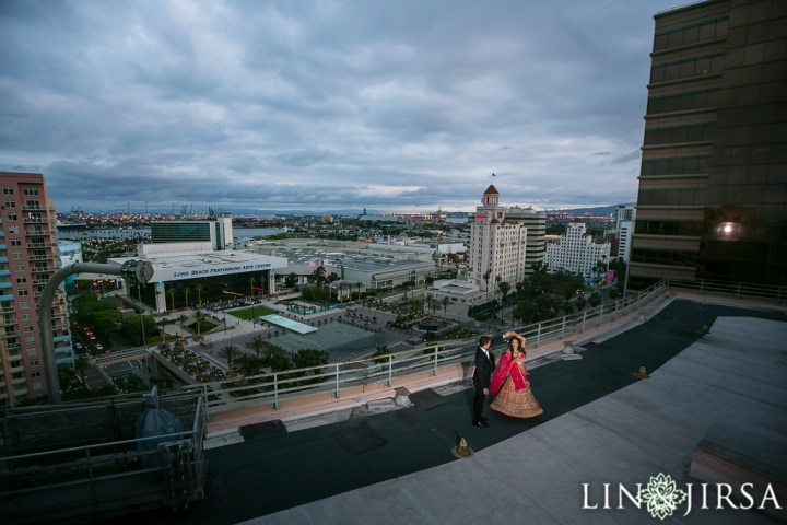 a couple dressed up for their wedding reception. The man is twirling his new bride who is wearing a lehenga; at the Westin Long Beach overlooking the Long Beach Performing Arts Center.