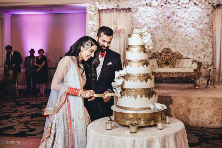 Indian couple cutting their wedding cake at their reception