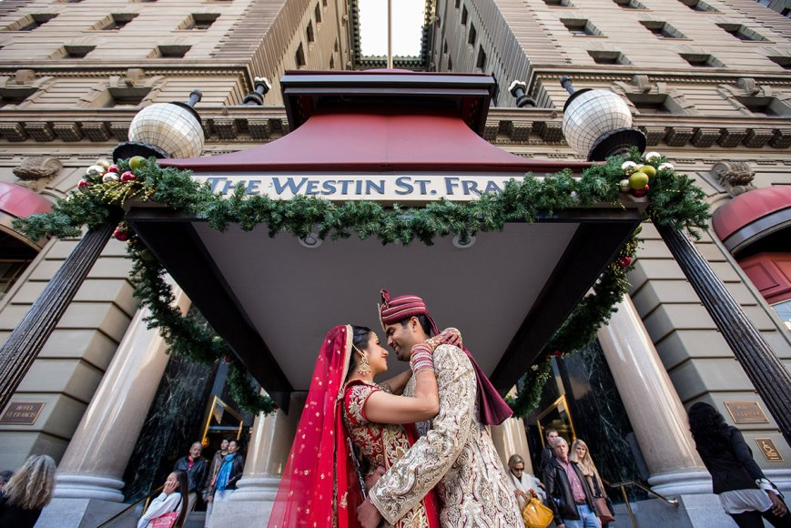 Indian couple standing outside The Westin St. Francis in San Francisco wearing Indian wedding attire