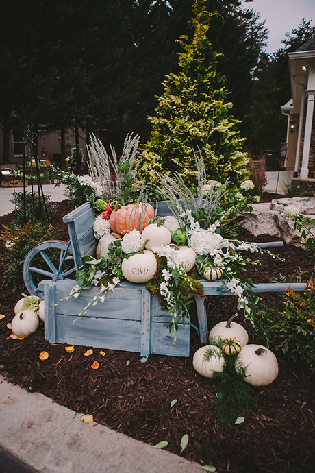 "pumpkins in wheelbarrow with ""Mr."" and ""Mrs."" written on them."