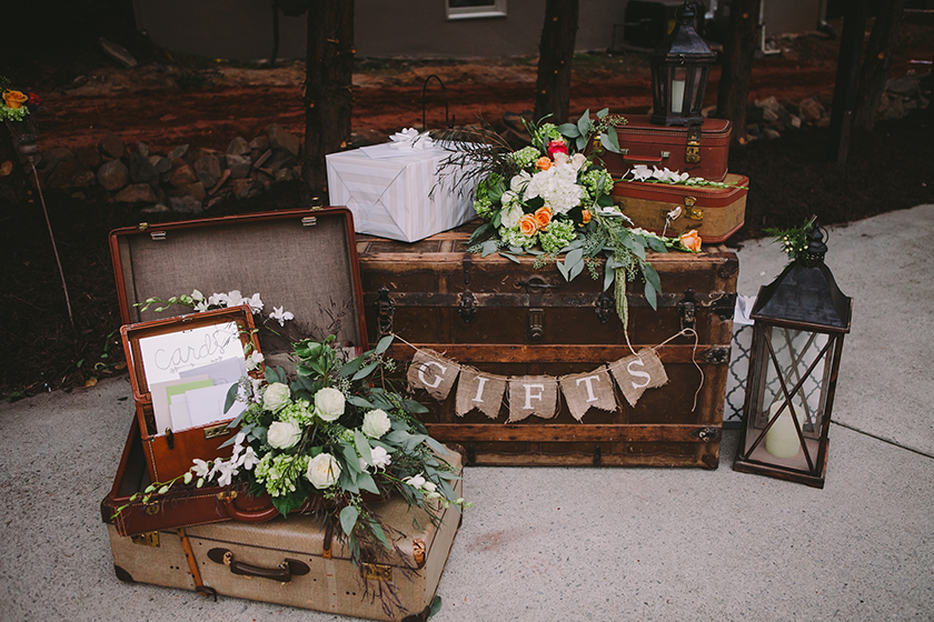 "old-fashioned suitcases and trunks with flowers on top and a sign that reads ""gifts."""