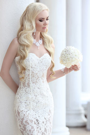 blonde woman with beach-y waves in her hair and in a mermaid-style wedding gown