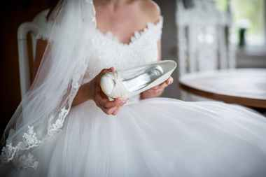 woman in white wedding dress holding unpaired white leather shoe