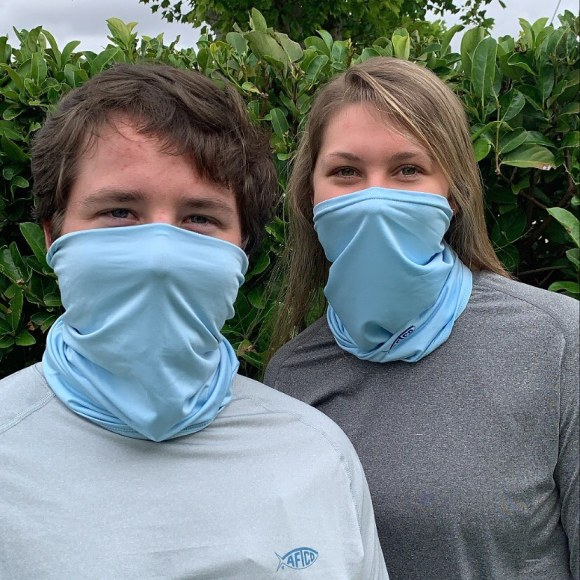 Man and woman wearing blue Aftco neck gaiters