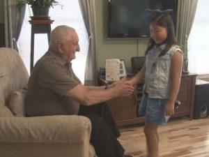 Young girl greets veteran.