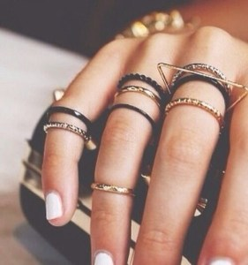 Gold and silver stacking rings on a hand.