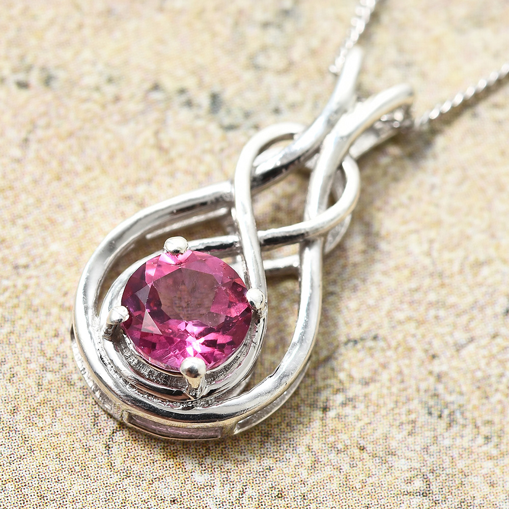 Closeup of pink gem pendant set in silver against brown marble counter