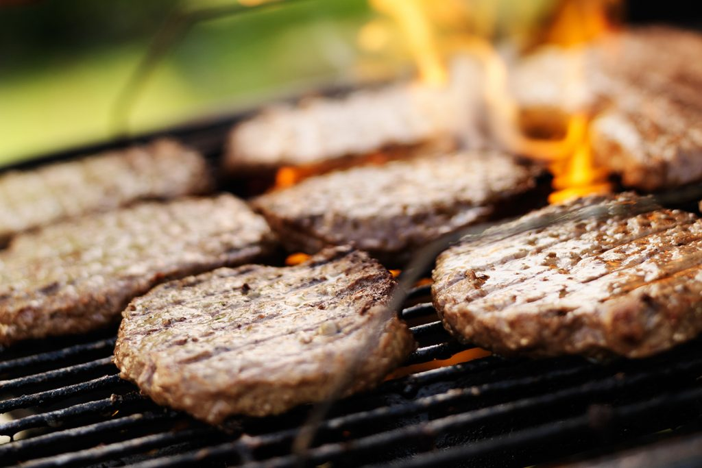 Hamburgers cooking on outdoor grill.